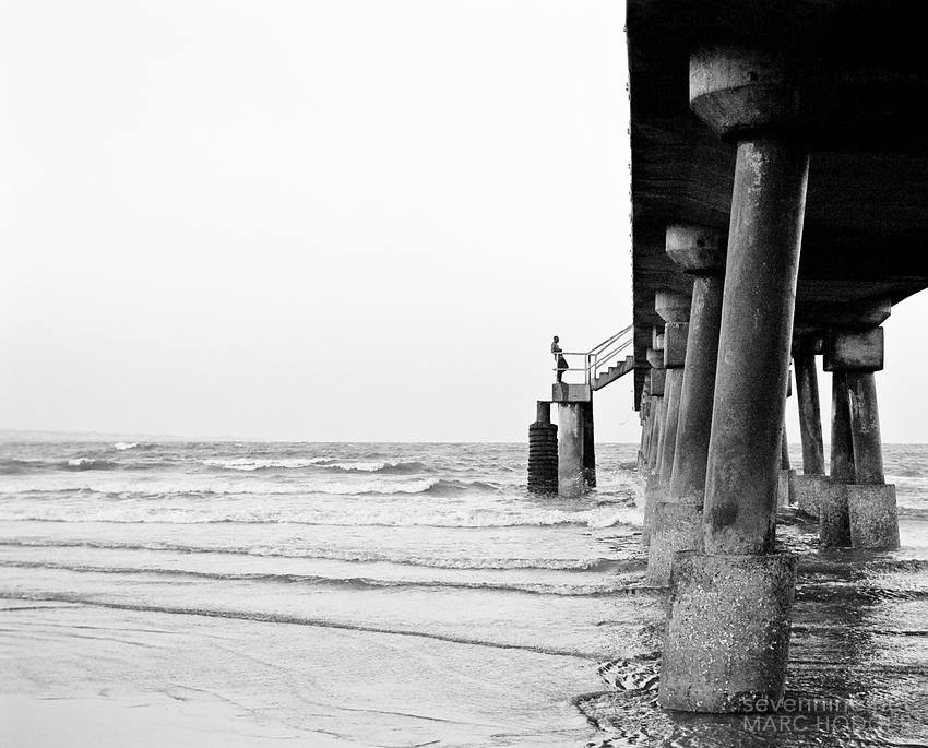 Man on Stairs of Pier